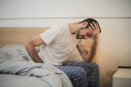 Man has stomach pain and holds head